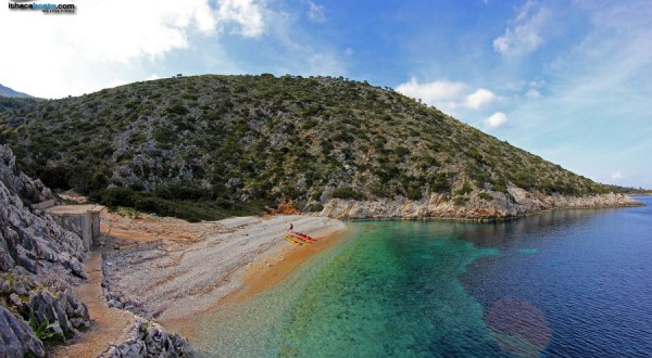 Photo of beach with rocks on Greek Ionian island with boats